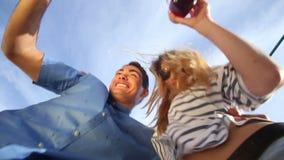 Pares novos loucos que olham para baixo na câmera, em cocktail bebendo e no riso video estoque