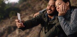Pares novos loving na caminhada que toma um selfie imagem de stock