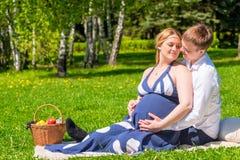 Pares novos loving que esperam um bebê, resto em um piquenique fotos de stock royalty free