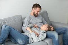 Pares novos loving que relaxam no sofá que aprecia o fim de semana em casa fotos de stock royalty free