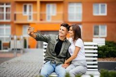 Pares novos na compra Pares novos consideráveis que sentam-se no banco e que tomam um selfie com um telefone celular fotografia de stock