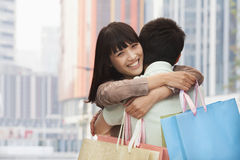Pares novos na compra indo do amor e em abraçar-se com os sacos de compras coloridos na rua, Pequim, China Imagem de Stock Royalty Free