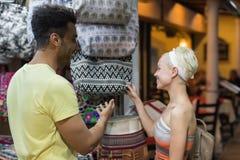 Pares novos na compra que escolhe o sorriso feliz do saco, do homem e da mulher na loja imagem de stock royalty free