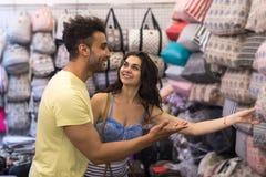 Pares novos na compra que escolhe o sorriso feliz do saco, do homem e da mulher na loja foto de stock royalty free