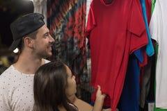 Pares novos na compra que escolhe o sorriso feliz dos compradores da roupa, do homem e de mulher na loja fotos de stock