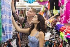 Pares novos na compra que escolhe o sorriso feliz dos compradores da roupa, do homem e de mulher na loja imagem de stock