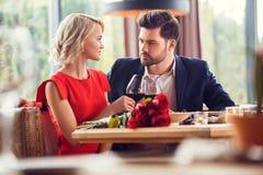 Pares novos na data em elogios de assento do restaurante com os vidros de vinho que olham se apaixonado foto de stock