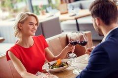 Pares novos na data no restaurante que senta-se tendo a fala bebendo dos elogios do vinho do almoço alegre imagens de stock