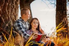 Pares novos na madeira do outono no piquenique e no livro de leitura Imagens de Stock