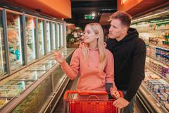 Pares novos na mercearia Levam o trole junto e olham ao saido Ponto da mulher em bolinhas de massa Compra e alimento fotos de stock royalty free