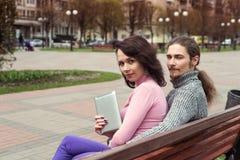Pares novos na moda dos estudantes na cidade usando a tabuleta Foto de Stock Royalty Free
