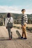 Pares novos na moda que t?m o divertimento com um skate na estrada imagens de stock royalty free