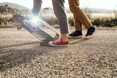Pares novos na moda que t?m o divertimento com um skate na estrada fotografia de stock royalty free