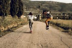 Pares novos na moda que t?m o divertimento com um skate na estrada fotos de stock