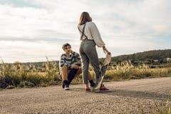 Pares novos na moda que t?m o divertimento com um skate na estrada foto de stock royalty free