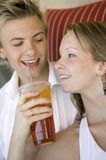 Pares novos na mulher do sofá que dá o fim congelado homem da bebida acima Imagens de Stock