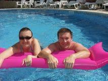 Pares novos na piscina Imagem de Stock