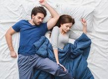 Pares novos na pose incômoda do conceito da manhã da opinião superior da cama fotografia de stock royalty free