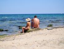 Pares novos na praia Imagem de Stock