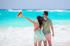 Pares novos na praia branca Férias de família imagem de stock