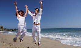 Pares novos na praia que salta para a alegria Imagem de Stock Royalty Free