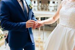 Pares novos nas alianças de casamento 1 do ouro da troca dos recém-casados do amor imagens de stock