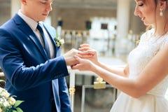 Pares novos nas alianças de casamento 1 do ouro da troca dos recém-casados do amor foto de stock royalty free