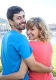 Pares novos nas camisas coloridas que fazem uma caminhada Imagem de Stock