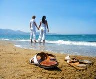 Pares novos nas mãos da terra arrendada da praia. foto de stock