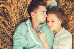 Pares novos no amor exterior Acople o aperto Pares bonitos novos no amor que fica e que beija no campo no por do sol Fotografia de Stock Royalty Free