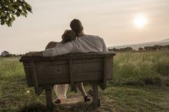 Pares novos no amor exterior no por do sol imagens de stock