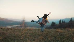 Pares novos no amor nas férias que apreciam montanhas O homem atrativo está levando a amiga em seus ombros e giros filme