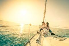 Pares novos no amor no barco de vela com champanhe no por do sol Fotografia de Stock Royalty Free