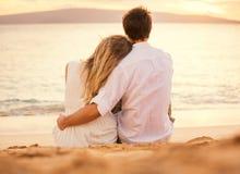 Pares novos no amor no por do sol da praia imagem de stock