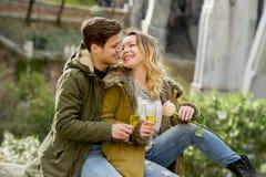 Pares novos no amor que beija maciamente na rua que comemora o dia ou o aniversário de Valentim que cheering em Champagne Fotografia de Stock Royalty Free