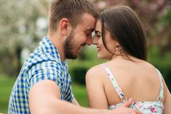 Pares novos no amor que descansa no jardim de florescência árvores de florescência do branco fotografia de stock