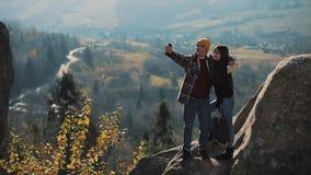 Pares novos no amor que está nas rochas e que toma um retrato do selfie Homem e mulher que visitam o turista famoso filme