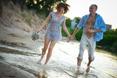 Pares novos no amor que funciona através da água que guardara as mãos Imagem de Stock