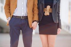 Pares novos no amor que guarda as mãos na rua Imagens de Stock Royalty Free