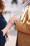 Pares novos no amor que guarda as mãos na rua Fotografia de Stock
