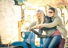 Pares novos no amor que tem o divertimento em uma bicicleta motorizada do 'trotinette' do vintage Fotografia de Stock Royalty Free