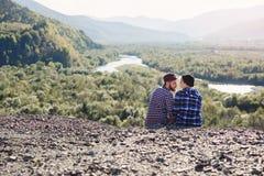 Pares novos no amor que viaja junto nas montanhas Homem feliz e menina do moderno que sentam-se junto na parte superior da montan fotos de stock