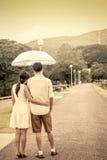 Pares novos no amor sob um guarda-chuva após a chuva Fotos de Stock Royalty Free