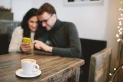 Pares novos no café que senta-se com smartphone e pares novos dentro Foto de Stock Royalty Free