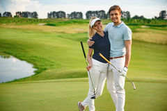 Pares novos no campo de golfe Fotografia de Stock