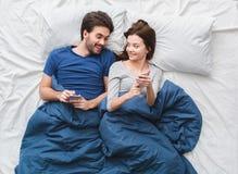 Pares novos no conceito da manhã da opinião superior da cama que ri da imagem no smartphone fotos de stock royalty free