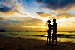 Pares novos no dia do casamento na praia tropical e no por do sol Fotografia de Stock