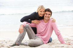 Pares novos no feriado que senta-se na praia do inverno Fotografia de Stock Royalty Free