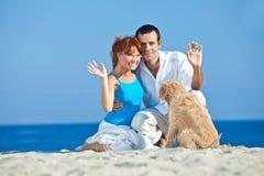 Pares novos no lado de mar que joga com seu cão Fotos de Stock