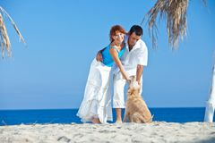 Pares novos no lado de mar que joga com seu cão Fotos de Stock Royalty Free